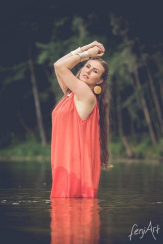 Fotoshooting mit fenjArt Fotografie model her name is king steht in einem orangefarbenem kleid in einem see