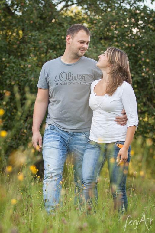 Paarshooting mit fenjArt Fotografie ein junges paar laeuft arm in arm durch eine sommerliche wiese
