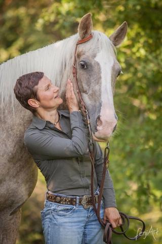 Pferdeshooting mit fenjArt Fotografie portrait von einem quarter horse und seiner reiterin im gruenen