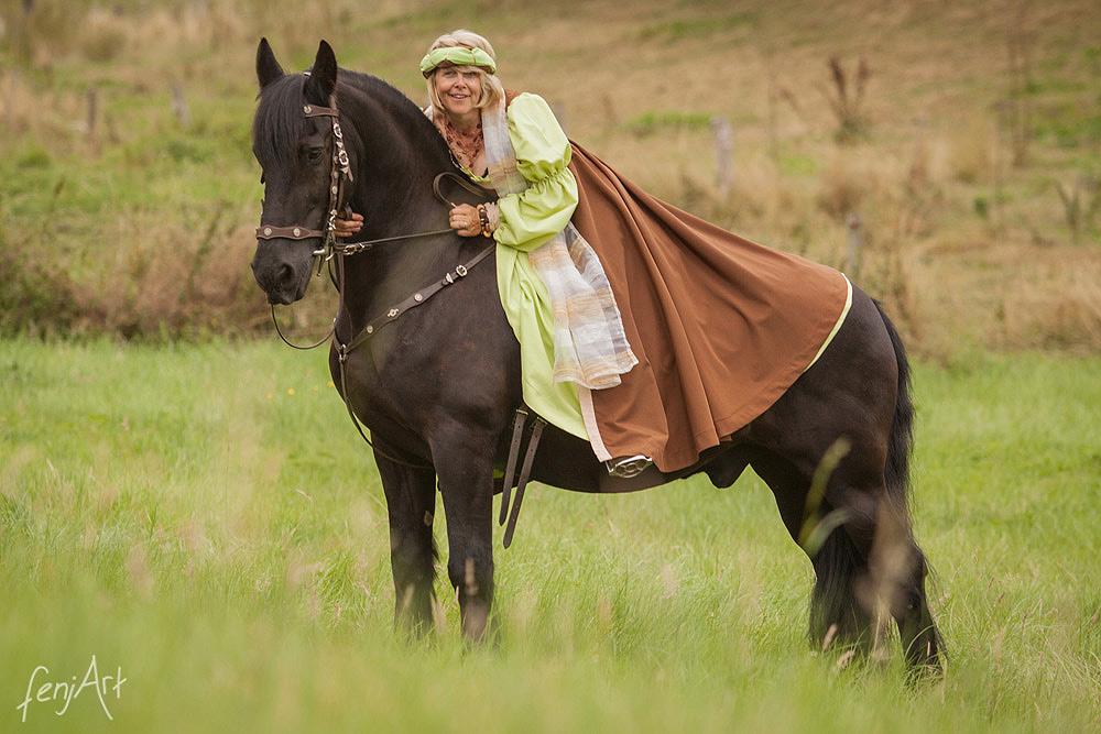 Pferdeshooting mit fenjArt Fotografie Blonde Reiterin sitzt in einem gruenen Kleid auf einem Friesenpferd