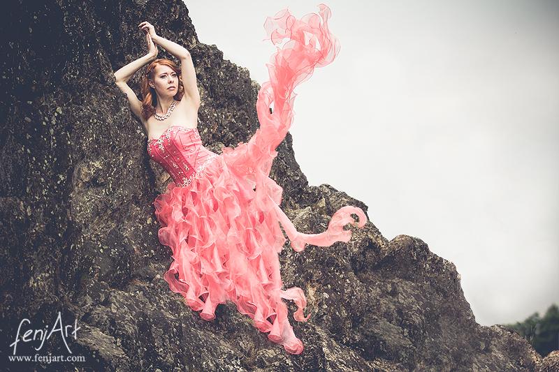 fenjArt Portraitfotografie - rothaarige frau steht mit wallendem rotem kleid in einer felswand