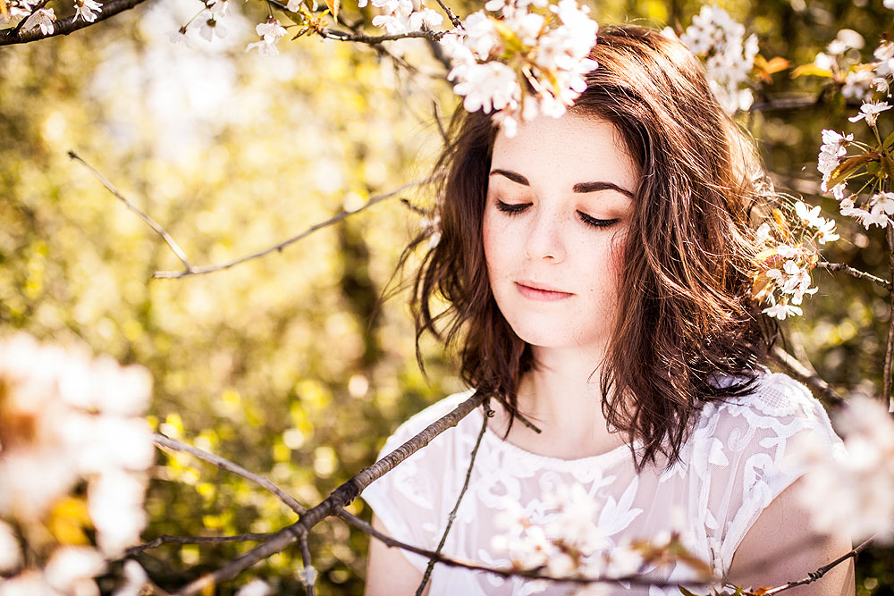 fenjart-com_blog-bilder_portraitshooting_braunhaarige-frau-steht-zwischen-bluehenden-aesten_lisa