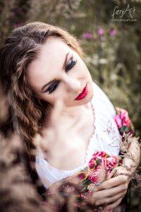 Portraitshooting mit fenjArt Fotografie braunhaarige frau hockt in einer blumenwiese und traeumt