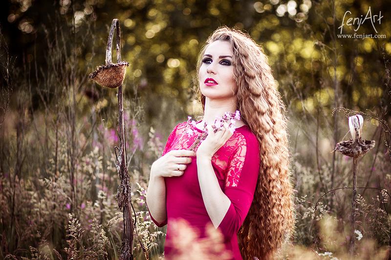 Portraitshooting mit fenjArt Fotografie langhaarige braunhaarige frau steht in einem feld aus getrockneten sonnenblumen im abendlicht