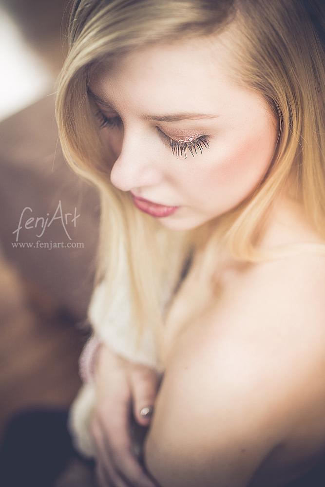 Boudoirshooting mit fenjArt Fotografie blonde frau sitzt sinnlich vertraeumt in ihrer wohnung und blickt an ihrer nackten schulter herab