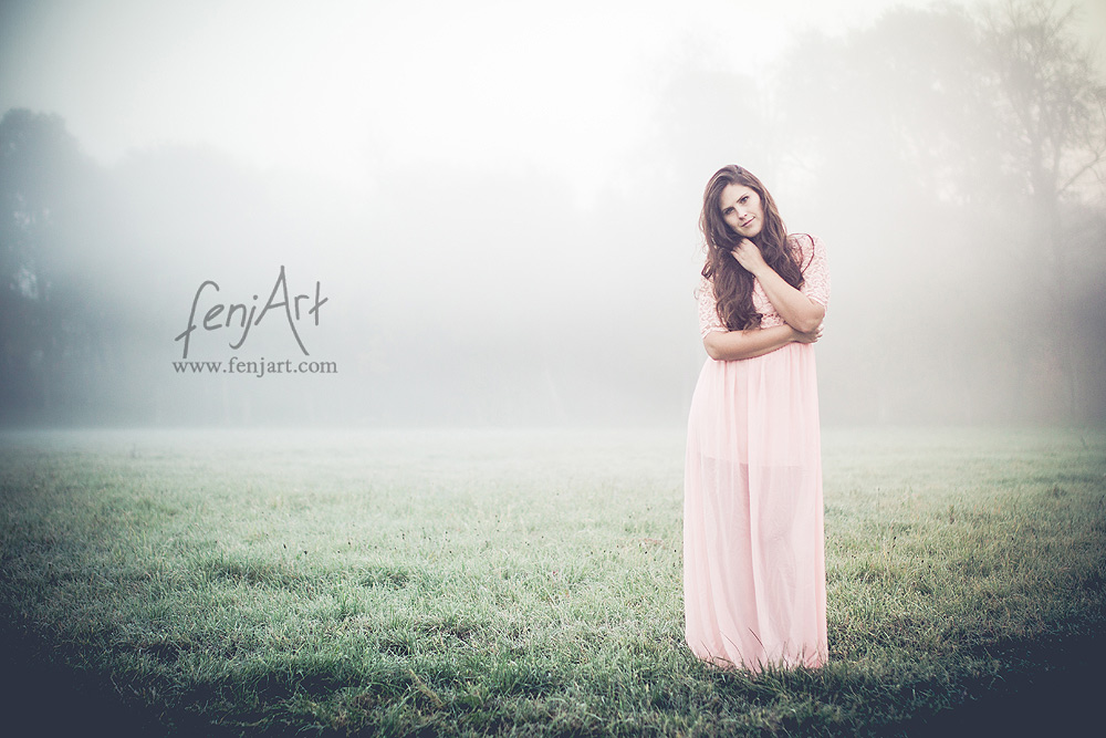 Fotoshooting mit fenjArt Fotografie braunhaarige frau steht in einem langen kleid im morgennebel auf einer wiese in zellhausen