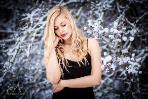 Portraitshooting mit fenjArt blonde frau steht in schwarzem kleid vor schneebedecktem gebuesch in frankfurt und stuetzt vertraeumt das gesicht in die hand