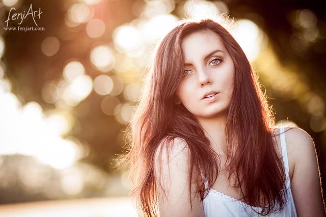 Portraitshooting mit fenjArt Fotografie braunhaarige Frau steht in weissem kleid im abendlicht bei seligenstadt