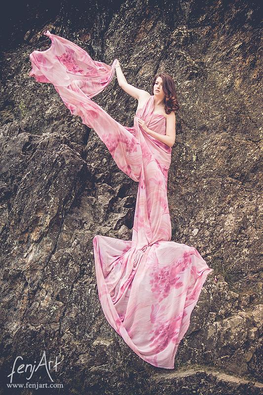 fenjArt Portraitfotografie - braunhaarige frau steht in einem rosafarbenem kleid mit wallendem tuch in einer felswand