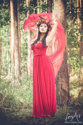 fenjArt Portraitfotografie - junge asiatische frau steht mit einem flammendroten kleid mit fliegendem schleier im wald