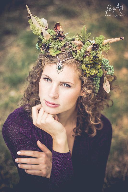 fenjArt Portraitfotografie - braunhaarige frau hockt mit intensivem blick und kopschmuck im wald