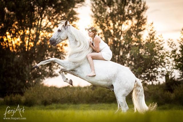 Pferdeshooting mit fenjArt reiterin in weissem kleid sitzt mit blumenkranz auf steigendem spanischen schimmel
