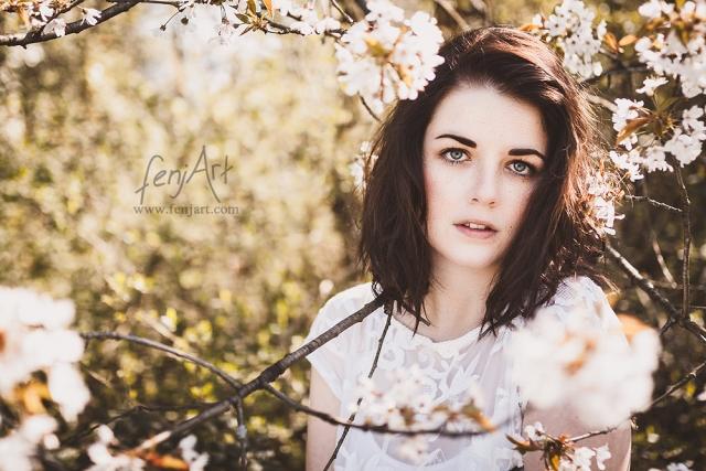 Fotoshooting mit fenjArt Fotografie braunhaarige frau schaut mit intensivem blick zwischen bluehenden bueschen hervor
