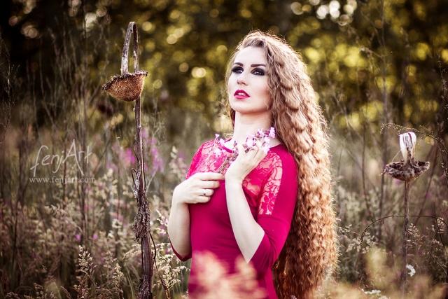 Fotoshooting mit fenjArt Fotografie bruenette frau mit langen haaren steht vertrauemt mit einem blumenstrauss in der hand im hohen gras