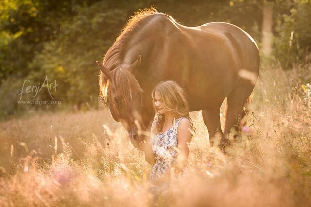 fenjArt Pferdefotografie - junge frau sitzt neben braunem pony im abendlicht in hohem gras