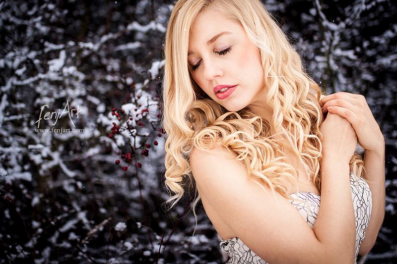 Fotoshooting mit fenjArt Fotografie blonde frau steht in hellem kleid bei schnee mit vertraeumt geschlossenen augen vor schnebedecktem gebuesch in frankfurt